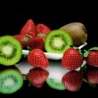 Kiwi and strawberries on plate on black background with mirr — Stock Photo #40341131