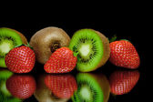 Ripe kiwi and strawberry on a black background with mirror refle — Stock Photo
