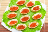 Tartlets with red caviar and butter on a plate — Stock Photo