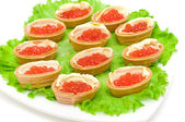 Tartlets with red caviar on a plate on white background — Stock Photo