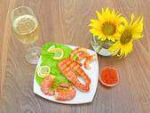 Gegrillter fisch mit zitrone, roter kaviar und shrimps, ein glas wein — Stockfoto