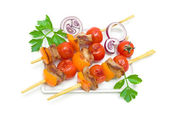 skewers of meat with vegetables on a plate isolated on a white  — Stockfoto