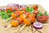 Kebab with vegetables and greens on a plate closeup. — Stock Photo