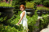 Woman walks in the lush garden at summer day — Stock Photo