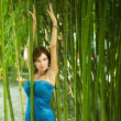 Woman with hands up in a green bamboo garden — Foto de Stock