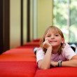 Little girl on a bench in a sunny room — Stock Photo