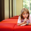 Little girl on bench in sunny room — Stock Photo #30565555