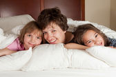Mother and two daughters in bed — Stock Photo
