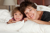 Mother and daughter in bed — Stock Photo