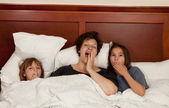Mother and two daughters in bed yawning — Stock Photo