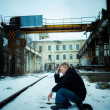 Man in depression sitting on rail in factory — Stock Photo
