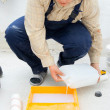 Stock Photo: Young worker pouring paint from a large bucket
