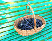 Purple green beans in the garden in a wicker basket — Stock Photo