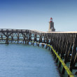 Постер, плакат: Wooden pier and lighthouse of the port of camps in normandy france