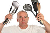 Man lost with kitchen utensils — Stock Photo