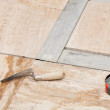 Workman's tools on a floor that is being tiled — Stock Photo #25586665