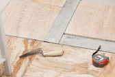Workman's tools on a floor that is being tiled — Stock Photo