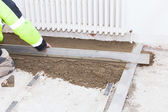 Mason leveling the cement screed — Stock Photo