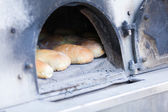 Traditional baking bread in a wood oven — Stock Photo