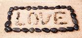 Slovo láska napsaný v písku pláže s oblázky — Stock fotografie