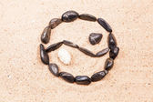 Yin yang drawn with pebbles on the sand — Stock Photo