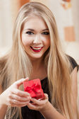 Beautiful young blond holding red gift box. — Fotografia Stock