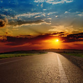 Red dramatic sunset over asphalt road — Stock Photo