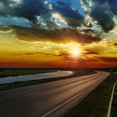 Dramatic sunset over asphald road — Stock Photo