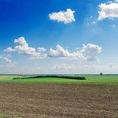 Black ploughed field under deep blue sky — Stock Photo