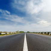 Road closeup under cloudy blue sky — Stock Photo