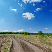 Winding rural road to horizon under cloudy sky — Stock Photo