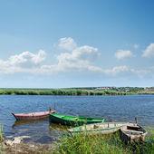 Rzeki i starych łodzi, w pobliżu zielonej trawie pod pochmurnego nieba — Zdjęcie stockowe