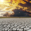 Dramatic sunset over dry cracked earth — Stock Photo #16255165
