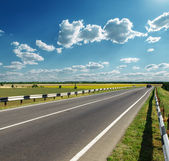 Asphalt road to horizon in cloudy sky — Stock Photo