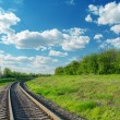 Railway goes to horizon in green landscape under blue sky with c — ストック写真