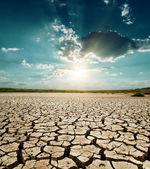 Dramático pôr do sol sobre a terra seca — Foto Stock