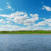 Clouds over river with green coast — Stock Photo