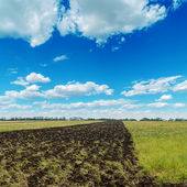 Blue cloudy sky and plouwed field — Stock Photo