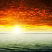 Ciel et rouge spectaculaire coucher de soleil sur mer — Photo