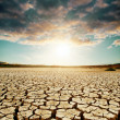 Global warming. dramatic sky over cracked earth — Stock Photo