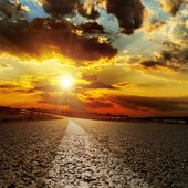 Asphalt road and dramatic sunset over it — Stock Photo