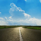 Asphalt road closeup under cloudy blue sky — Stockfoto