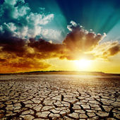 Global warming. dramatic sunset over cracked earth — Stock Photo