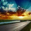 Fantastic dramatic sunset over asphalt road — Stock Photo
