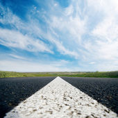 White line on asphalt road close up and cloudy sky — Stock Photo