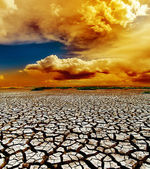 Dramatic sunset over dry cracked earth — Stock Photo