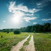 Sol och moln över vägen till trä — Stockfoto