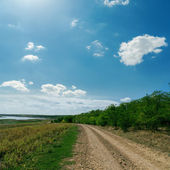 Rural road goes to horizon under cloudy sky — Stock Photo