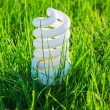 White energy saving bulb in green grass — Stock Photo