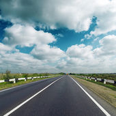 Asphalt road under dark cloudy sky — Stock Photo